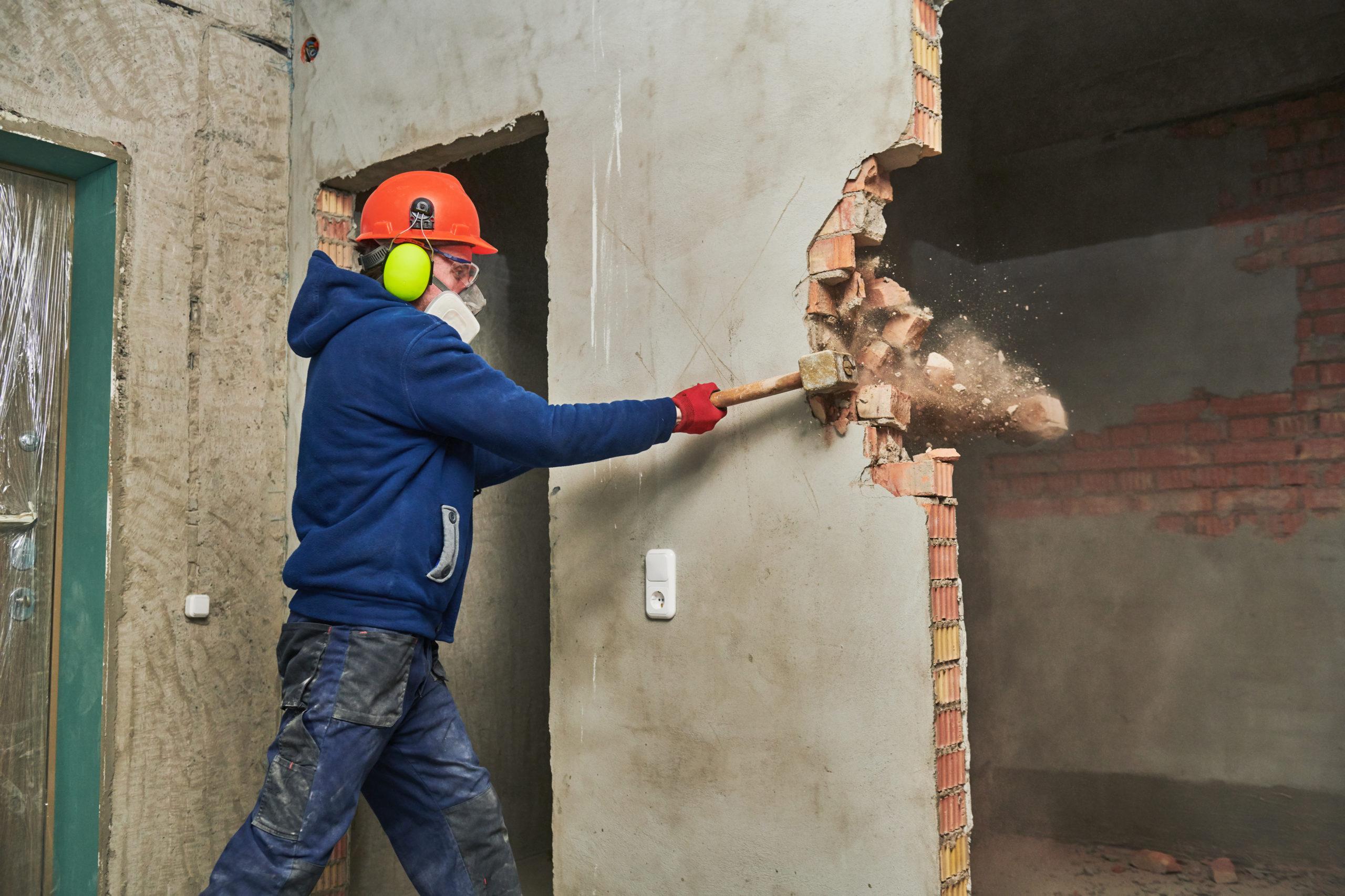 demolition work. Worker builder with sledgehammer destroying interior wall. Rearrangement during renovation. slow motion